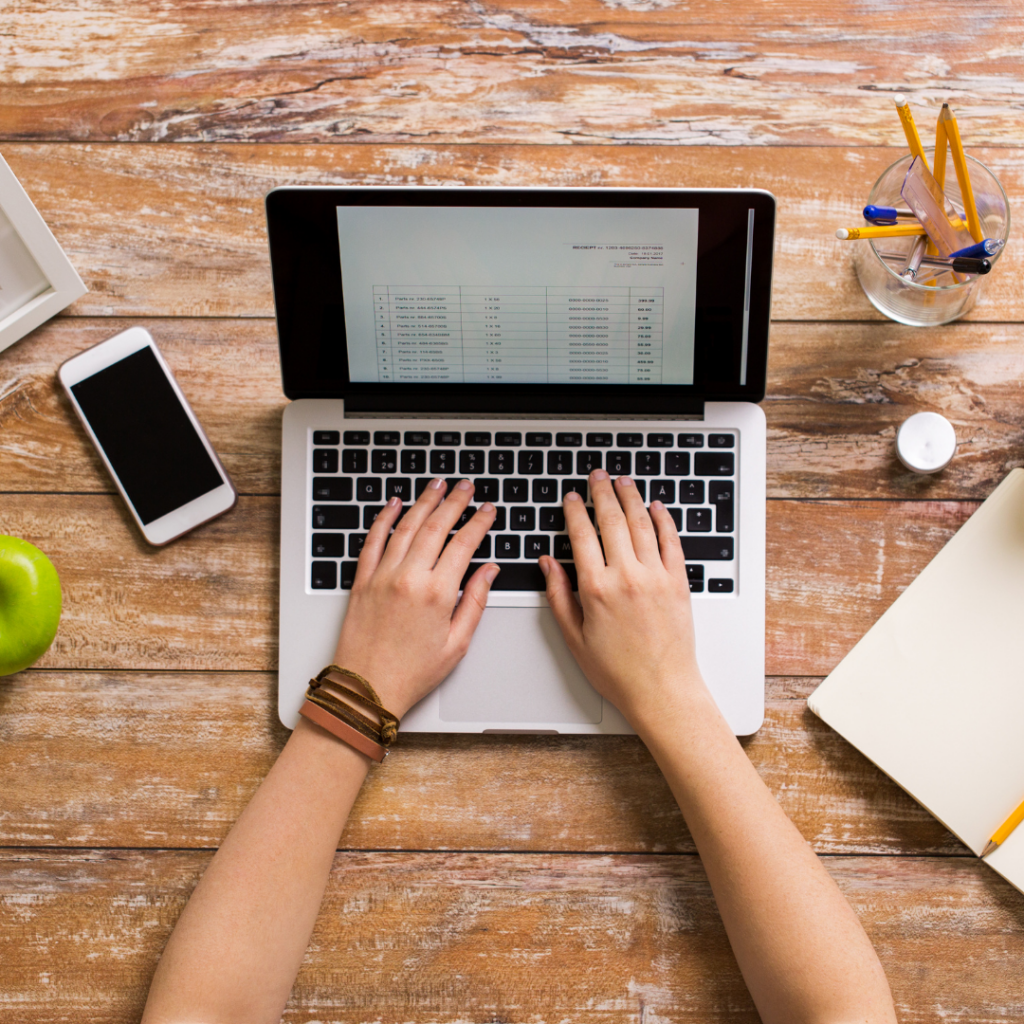 woman's hands hovering over laptop computer. iphone to the left, next to a green apple. to the right of the laptop, and open blank notebook. All on top of a wooden plank desktop.